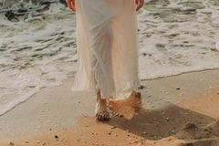 Young woman in white dress walking on the beach stock photos
