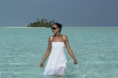 Young woman in a white dress walking in turquise water Maldives Stock Photo