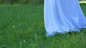 A young woman in a white dress walks on the grass barefoot. Summer day stock video