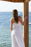 Young woman in white dress watching ship on the sea. Standing girl looking at the ocean Royalty Free Stock Photos