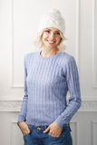 Young woman in a white hat and a blue sweater Stock Photography