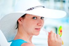 Young  woman in white hat drinking a cocktail Stock Photography