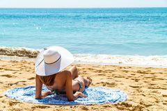 Young Woman With White Hat Relaxing On Beach stock photography