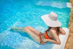 Young woman in white hat resting in pool Stock Photos