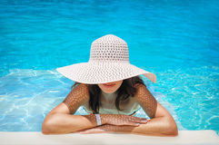 Young woman in white hat resting in pool Stock Image