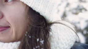 Young woman in a white hat. And a scarf and snow on her hair close-up stock video