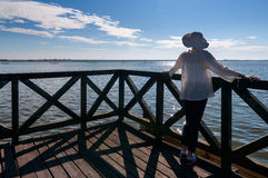 Young woman in white hat standing on wooden pier Stock Images