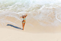 Young woman with white hat stands on ocean sand Stock Photography