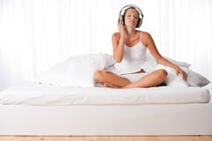 Young woman in white with headphones Stock Photo