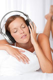 Young woman in white with headphones Stock Image