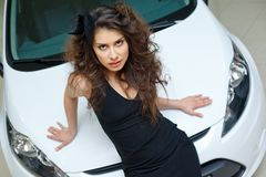 Young woman on white hood of New car Stock Photography