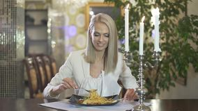 Young blonde woman in white jacket eating italian cuisine pasta spaghetti alone in fancy restaurant making funny face. Young woman in white jacket eating italian stock footage