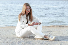Young woman in the white jacket is sitting and looking at the camera Stock Images