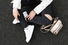Young woman in a white jacket in stylish ripped black jeans with a gold trendy backpack in fashionable leather sneakers sits. On the asphalt. Details of royalty free stock image