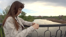 A young woman in a white jacket uses a phone on the city bridge. stock footage