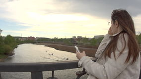 A young woman in a white jacket uses a phone on the city bridge. stock video footage
