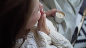 Young woman in a white knit sweater holds in her hands and drinks coffee close-up over her shoulder. 4k stock video