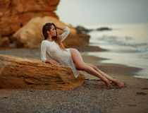 Young woman in white lacy dress lies on rock on pebble beach by Royalty Free Stock Photo