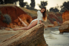 Young woman in white lacy dress lies on rock by the sea. Royalty Free Stock Photos