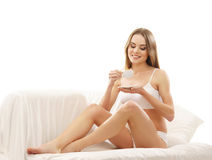 A young woman in white lingerie holding a cup Stock Images