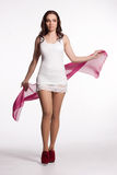 Young woman in a white mini dress, red heels with pink scarf Royalty Free Stock Images