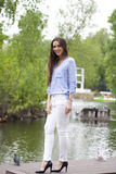 Young woman in white pants and a blue blouse. Happy young brunette woman in white pants and a blue blouse in the summer park stock photos