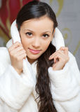 Young woman in a white robe Stock Images