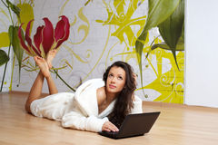 A young woman in a white robe with laptop Royalty Free Stock Image