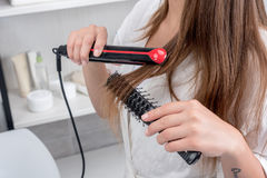 Young woman in white robe using hair straightener in bathroom Stock Photography
