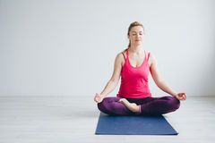 Young woman in a white room doing yoga exercises . Royalty Free Stock Image