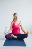 Young woman in a white room doing yoga exercises . Royalty Free Stock Photos