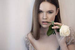 Young woman with white rose in her mouth Stock Images