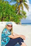 Young woman on white sand beach on Maldives Stock Photo