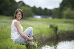 Young woman in white seated at the lake Stock Images