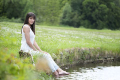 Young woman in white seated at the lake Royalty Free Stock Image