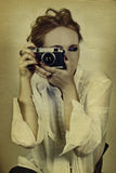 Young woman in white shirt. Taking picture with vintage film camera on grunge background Stock Photography