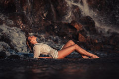 Young woman in white shirt and bikini lies on rock near waterfal Stock Photography