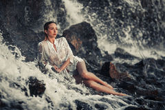 Young woman in white shirt and bikini lies on rock in water flow royalty free stock photos