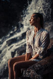 Young woman in white shirt and bikini sits on rock near waterfal. L. Around visible water flows, spray and foam. She`s wet Royalty Free Stock Image