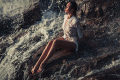 Young woman in white shirt and bikini sits on rock in water flow. Young woman in white shirt and bikini sits on rock near waterfall. Around visible water flows Royalty Free Stock Photos