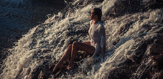 Young woman in white shirt and bikini sits on rock in water flow Stock Photography