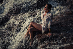 Young woman in white shirt and bikini sits on rock in water flow. Young woman in white shirt and bikini sits on rock near waterfall. Around visible water flows Royalty Free Stock Image