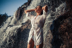 Young woman in white shirt and bikini stands near waterfall. Around visible water flows, spray and foam. She`s wet Royalty Free Stock Image