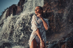 Young woman in white shirt and bikini stands near waterfall. Around visible water flows, spray and foam. She`s wet Royalty Free Stock Photography