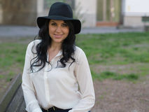 Young woman in a white shirt and black hat Stock Photography