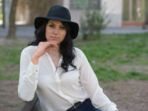 Young woman in a white shirt and black hat Stock Image