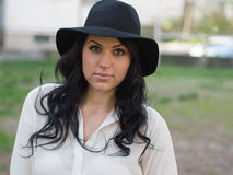 Young woman in a white shirt and black hat Royalty Free Stock Image