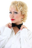 Young woman in white shirt correcting a bow-tie. Young blondie woman in white shirt correcting a bow-tie Royalty Free Stock Photo