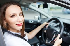 Young woman driving car on the road. Young woman in white shirt driving car on the road. Hispanic girl steering wheel in auto royalty free stock photos