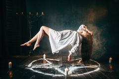 Woman in white shirt flying over pentagram circle. Young woman in white shirt flying over pentagram circle, gark magic, sacrificial ritual. Occultism and royalty free stock photo